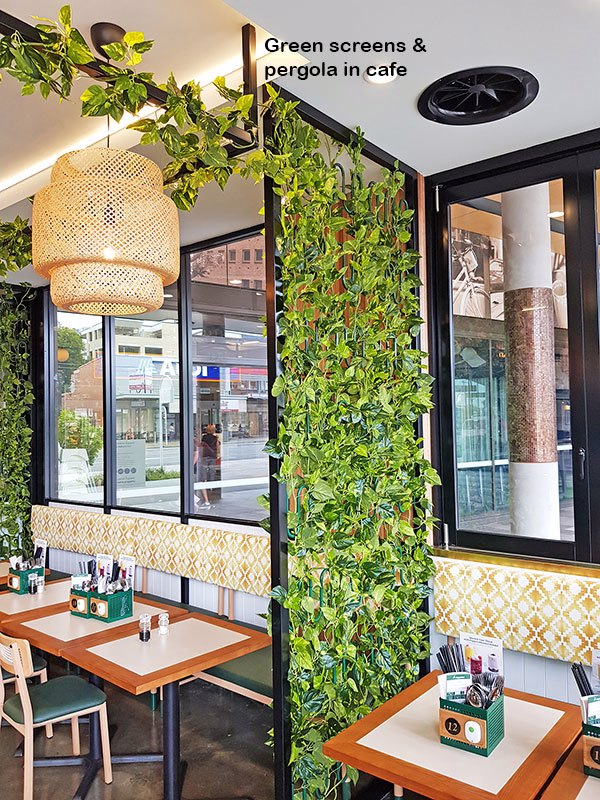 Cafe uses artificial green-vines for privacy screens & pergolas